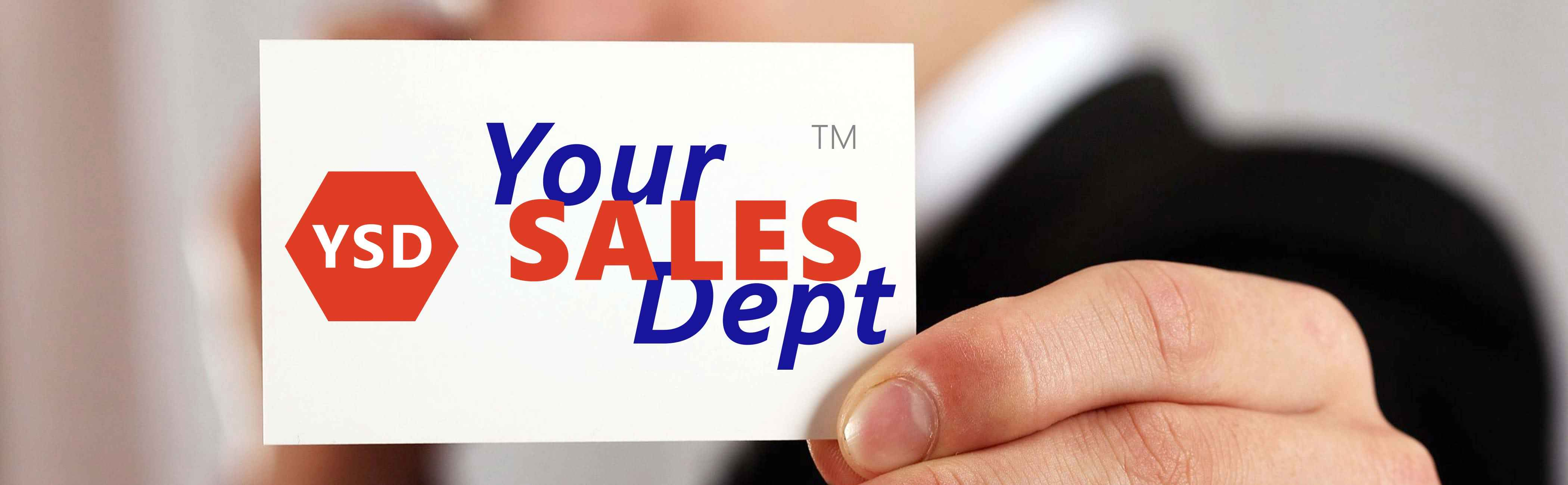 Businessman holding a Your Sales Dept business card.