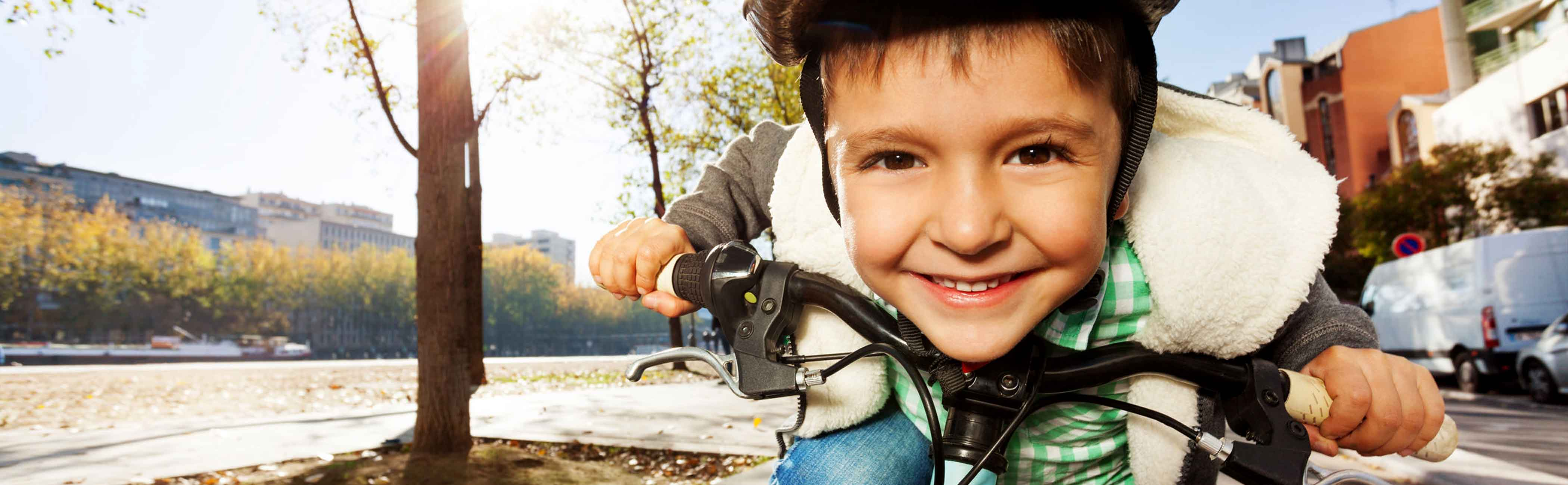 A young boy smiling as he zooms on his bike.