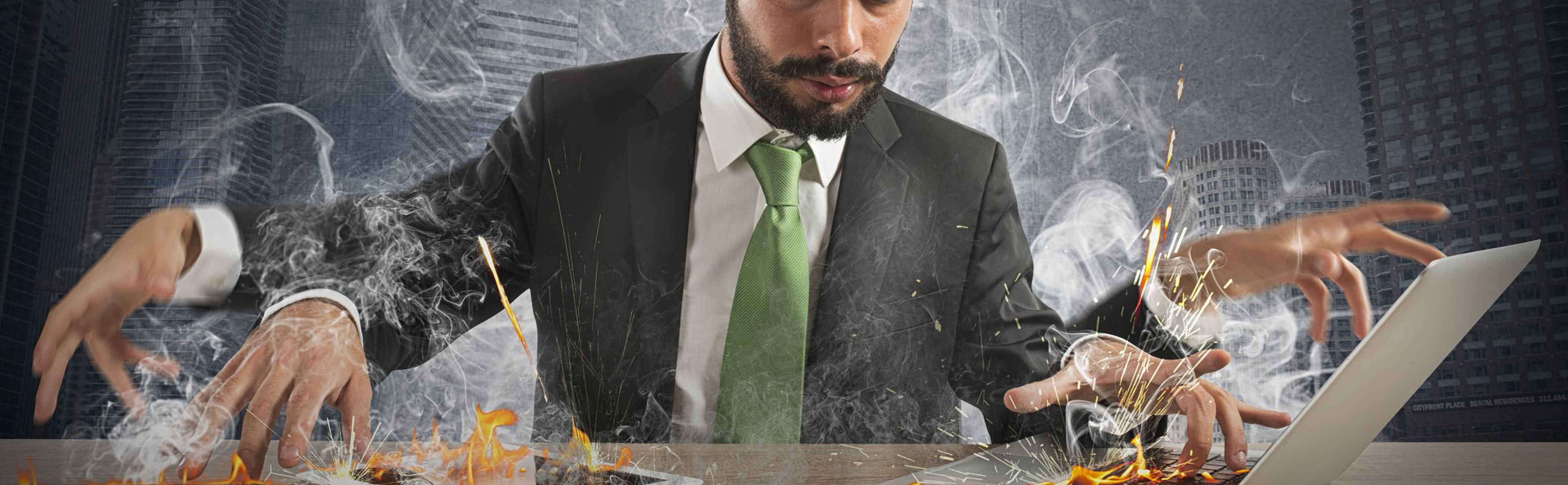 Businessman working so fast, flames lick out of his computer and phone.